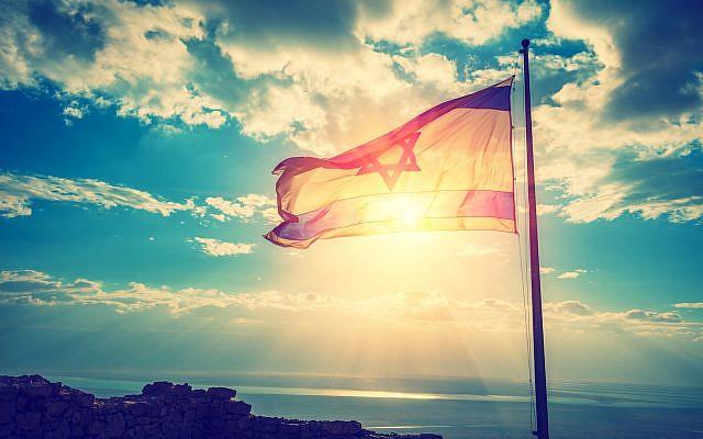 Le drapeau israélien vole sur Massada dans le ciel du matin (Crédit : iStock)