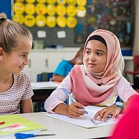 Illustration : une écolière vêtue d'un hijab à côté d'une camarade de classe. (Crédit : Ridofranz via iStock)