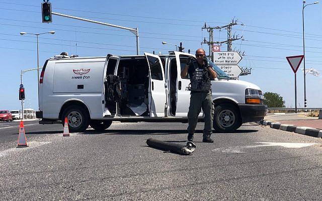 Un démineur de la police est vu près d'une roquette qui a atterri sur la route 4, une route principale près d'Ashkelon (Crédit : police israélienne)