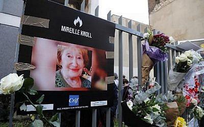 Une photo de Mireille Knoll, survivante de la Shoah, assassinée, et des fleurs sont placées sur la clôture entourant son immeuble à Paris, le 28 mars 2018. (Crédit : François Guillot / AFP)