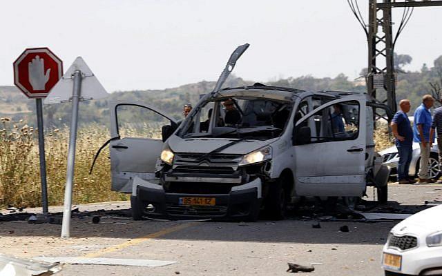 Des Israéliens autour d'une voiture touchée par un missile anti-tank lancé depuis Gaza, qui a tué un Israélien, près de Yad Mordechai, au sud d'Israël, le 5 mai 2019. (Crédit : Jack GUEZ / AFP)