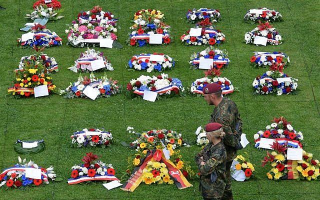 Des soldats allemands devant les gerbes de fleurs au cimetière militaire allemande à la Cambe, le 5 juin 2019. (Crédit : JEAN-FRANCOIS MONIER / AFP)