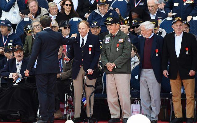 Le président français Emmanuel Macron salue des vétérans américains après leur avoir remis la Légion d'Honneur au cimetière américain de Coleville sur mer, le 6 juin 2019. (Crédit : Damien MEYER / AFP)