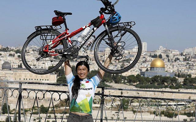 Le cycliste taïwanais qui fait le tour du monde, pose avec son vélo sur le mont des Oliviers, qui surplombe la Vieille Ville de Jérusalem, le 10 juin 2019. (Crédit : MENAHEM KAHANA / AFP)