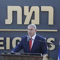 """Le Premier ministre Benjamin Netanyahu prononce un discours devant le panneau de la nouvelle communauté établie au nom de """"Ramat Trump"""", """"colline  Trump"""" en français, qui porte le nom du président américain, durant une cérémonie officielle, le 16 juin 2019 (Crédit : Jalaa MAREY/AFP)"""