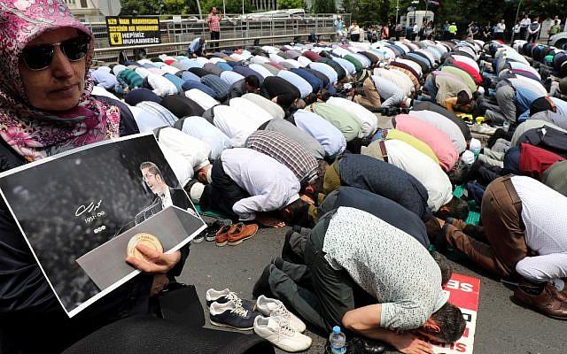 Une femme tient une photo de Mohamed Morsi lors d'une prière pour les funérailles du président, devant l'ambassade d'Ankara, le 18 juillet 2019. (Crédit : Adem ALTAN / AFP)