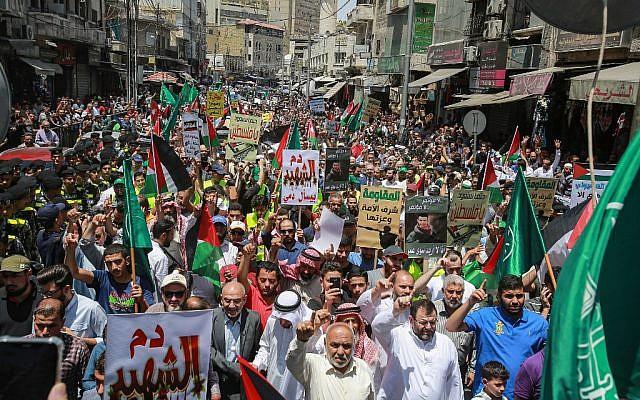 """Les drapeaux jordaniens et des frères musulmans brandis parmi d'autres, dénonçant la conférence économique organisée par les Etats-Unis au Bahreïn au cours d'une manifestation contre """"l'accord du siècle"""" du président Donald Trump, à Amman, capitale de la Jordanie, le 21 juin 2019 (Crédit : Khalil MAZRAAWI / AFP)"""
