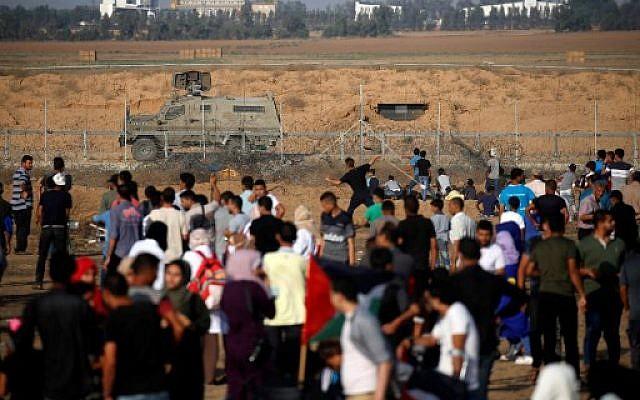Un Palestinien lance des objets avec une fronde de l'autre côté de la clôture frontalière avec Israël lors d'affrontements avec les soldats israéliens, à l'est de Khan Yunis, dans la bande de Gaza, le 21 juin 2019 (Crédit :  Said KHATIB / AFP)