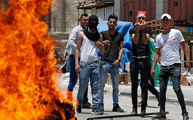 Des Palestiniens tenant des pierres derrière un pneu en feu lors d'affrontements après une manifestation contre le sommet sur le conflit israélo-palestinien organisé par les États-Unis au Bahreïn, dans le village de Halhul, aux environs de Hébron, le 24 juin 2019. (Crédit : HAZEM BADER / AFP)