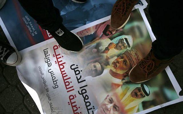 Des Palestiniens marchent sur une pancarte arborant les photos du prince héritier d'Abu Dhabi Sheikh Mohammed bin Zayed, du prince héritier saoudien Mohammed bin Salman, du roi du Bahreïn Hamad al-Khalifa, du sultan d'Oman  Sultan Qaboos à Muscat, du Premier ministre israélien Benjamin Netanyahu, du président américain Donald Trump et de son gendre et conseiller Jared Kushner, au cours d'une manifestation contre la conférence économique organisée au Bahreïn par les Etats-Unis, le 24 juin 2019 à Gaza (Crédit : MOHAMMED ABED / AFP)