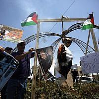 Des Palestiniens brûlent un mannequin à l'effigie de Donald Trump à Bethléhem pour protester contre le sommet à Bahreïn sur le volet économique du plan de paix proposé par l'administration Trump, le 25 juin 2019. (Crédit :  Al SHAER / AFP)