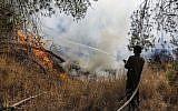 Un soldat israélien éteint un feu causé par un ballon incendie lancé depuis Gaza, près du kibboutz Nahal Oz, le 26 juin 2019. (Crédit : Menahem Kahana/AFP)