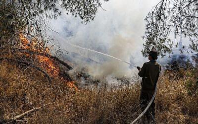 Un soldat israélien éteint un feu causé par un ballon incendiaire lancé depuis Gaza, près du kibboutz Nahal Oz, le 26 juin 2019. (Crédit : Menahem Kahana/AFP)