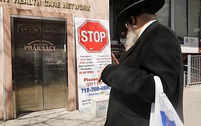 Un panneau mettant en garde la communauté juive ultra-orthodoxe contre une épidémie de rougeole devant une parmacie du quartier de Williamsburg, le 10 avril 2019. (Crédit : Spencer Platt/Getty Images/AFP)