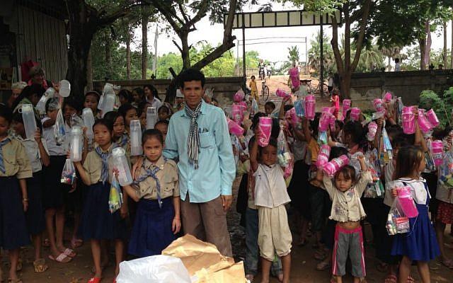 Arun Sothea dirige un orphelinat au Cambodge avec l'aide d'organisations caritatives juives. Ici, il distribue des fournitures aux petites filles dans son village de Phum Thom (Autorisation : Arun Sothea)