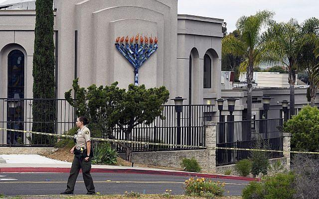 Un shérif adjoint du comté de San Diego se tient devant la synagogue Habad à Poway, en Californie, le 28 avril 2019, après une fusillade. (Crédit : AP/Denis Poroy)