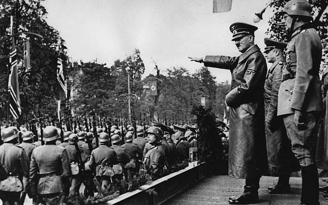 Adolf Hitler, devant, salue les militaires de la  Wehrmacht allemande qui défilent à Varsovie, en Pologne, au mois d'octobre 1939, après l'invasion allemande. Derrière, de gauche à droite : Le commandant en chef de l'armée, le  Colonel Général Walther von Brauchitsch, le nouveau commandant de Varsovie, le Lieutenant Général Friedrich von Cochenhausen, le Colonel Général Gerd von Rundstedt,  le Colonel Général Wilhelm Keitel. (Crédit : AP Photo)