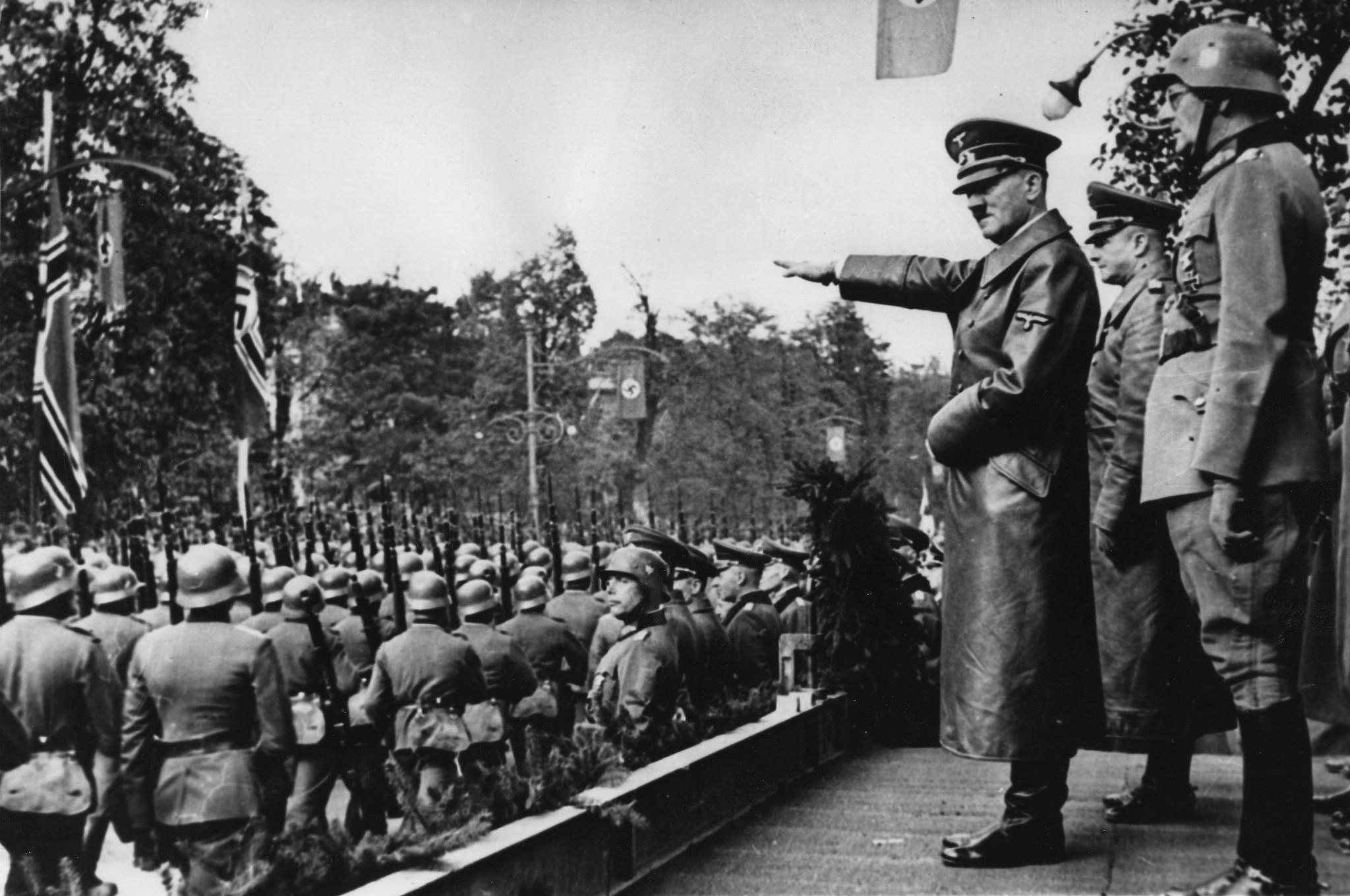 Adolf Hitler, (au centre), salue les troupes de la Wehrmacht allemande qui défilent à Varsovie, en Pologne, au mois d'octobre 1939, après l'invasion allemande. Derrière, de gauche à droite: Le commandant en chef de l'armée, le  Colonel Général Walther von Brauchitsch, le nouveau commandant de Varsovie, le Lieutenant Général Friedrich von Cochenhausen, le Colonel Général Gerd von Rundstedt, le Colonel Général Wilhelm Keitel. (Crédit : AP Photo)