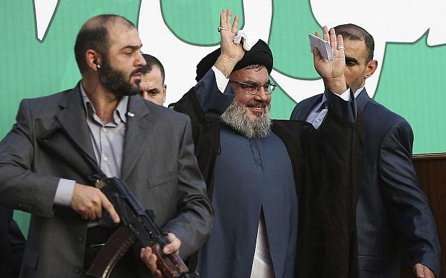 Le leader du Hezbollah Hassan Nasrallah escorté par ses gardes du corps devant des dizaines de milliers de partisans lors d'un rassemblement à Beyrouth, au Liban, le 17 septembre 2012 (Crédit : AP Photo/Hussein Malla, File)