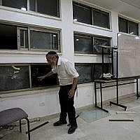 Un rabbin à l'intérieur d'une école religieuse de Sderot, en Israël, après qu'elle a été touchée par une roquette tirée depuis la bande de Gaza, le 13 juin 2019 (Crédit : AP/Tsafrir Abayov)