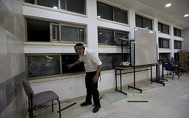 Un rabbin à l'intérieur d'une école religieuse de Sderot, en Israël, après qu'elle a été touchée par une roquette tirée depuis la bande de Gaza, le 13 juin 2019. (Crédit : AP/Tsafrir Abayov)