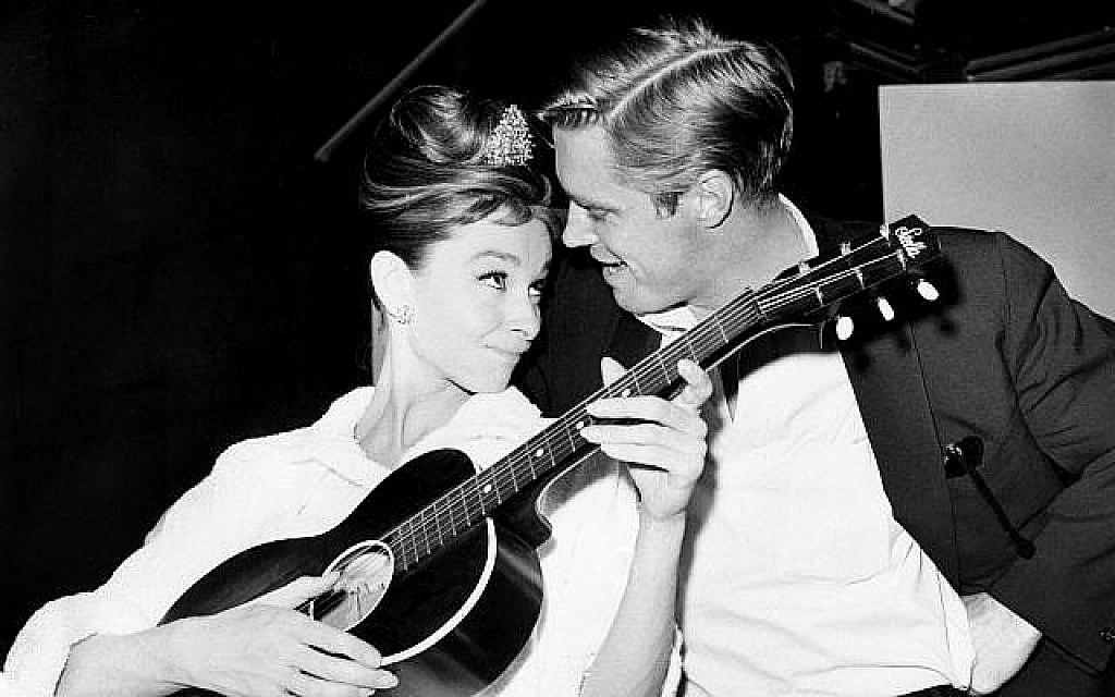"""Audrey Hepburn à la guitare aux côtés de George Peppard entre deux prises sur le tournage de """"Diamants sur canapé"""" dans un studio de Hollywood, le 7 décembre 1960 (Crédit : AP Photo)"""