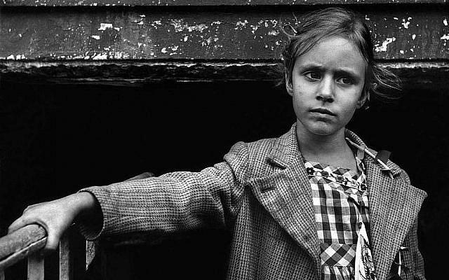 Zoom sur une photo d'une petite fille vêtue d'une robe vichy et d'un manteau en tweed à col large se tenant à une rampe, à New York, 1957. (Harold Feinstein/autorisation)