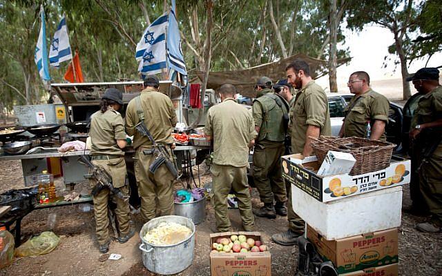 A titre d'illustration : Des soldats de réserve de Tsahal en train de recevoir de la nourriture dans une zone de transit près de la frontière avec Gaza, dans le sud d'Israël, le 20 juillet 2014, lors de l'opération Bordure protectrice menée par Israël. (Moshe Shai/Flash90)