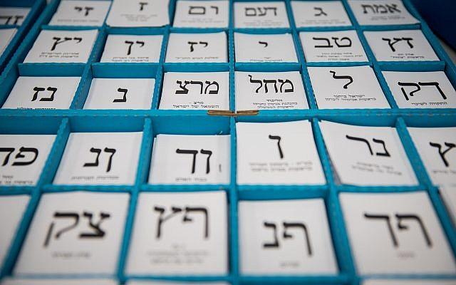 Un présentoir de bulletins de vote se trouve devant un isoloir à l'occasion des élections législatives israéliennes du 9 avril 2019. (Hadas Parush/Flash90)