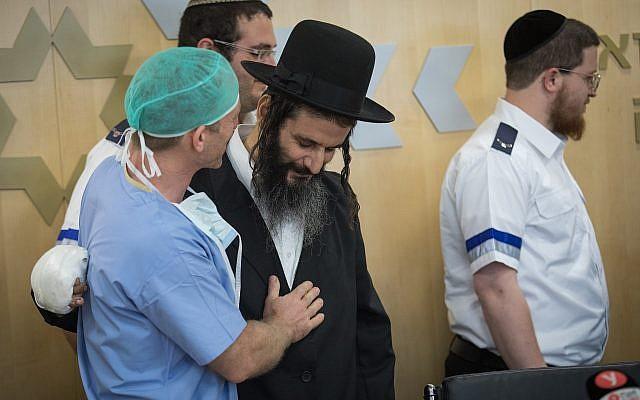 Gabriel Lavi, (au centre), en compagnie de ses médecins et secouristes qui lui ont fourni leur aide, fait une déclaration à la presse avant sa sortie de l'hôpital Shaare Zedek de Jérusalem, le 12 juin 2019. (Hadas Parush/Flash90)