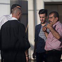 L'avocat Nashaf Darwish (g) parle avec le frère et le fils de Mahmoud Qadusa, un Palestinien suspecté du rapt et du viol du fillette israélienne de 7 ans, devant un tribunal miliatre de Cisjordanie, le 19 juin 2019. (Crédit : Yonatan Sindel/Flash90)