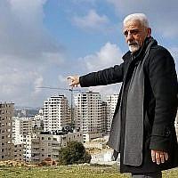 Munir Zughayer, un activiste qui dirige un comité qui se plaint souvent de la situation des services à Kafr Aqab auprès de la municipalité de Jérusalem, pointe du doigt un certain nombre de bâtiments construits en violation de la réglementation le 20 février 2019. (Crédit : Adam Rasgon / Times of Israël)