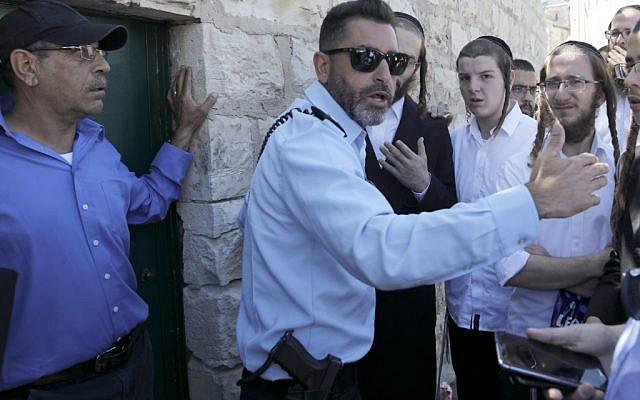 Un policier israélien empêche des hommes juifs ultra-orthodoxes d'entrer dans le site du Tombeau des Rois possédé et administré par le consulat français de Jérusalem parce qu'ils n'ont pas pré-enregistré leur visite à travers le site internet qu'ils n'utilisent pas pour des raisons religieuses, à Jérusalem est le 27 juin 2019. (Photo par MENAHEM KAHANA / AFP)
