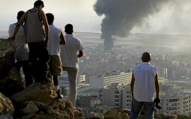 Sur cette photo datée du 14 juillet 206, des jeunes libanais sont rassemblés sur une colline surplombant la ville de Beyrouth au Liban au coucher du soleil afin d'observer la fumée qui s'échappe d'un réservoir de carburant à l'aéroport international de Beyrouth, qui a été touché par une frappe israélienne. (AP Photo/Ben Curtis)