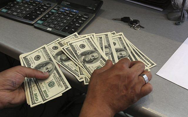 Un employé d'un bureau de change compte des dollars américains dans le centre-ville de Téhéran, en Iran, le 9 juin 2011. (AP/Vahid Salemi)
