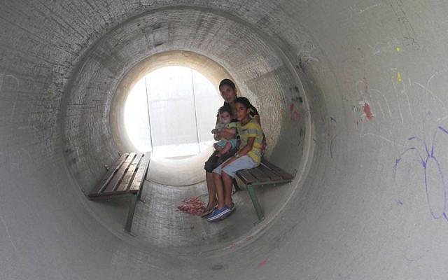 Une famille israélienne s'abrite dans un abri anti-bombe reconverti à partir d'un conduit en béton lors de la guerre de 2014 à Gaza. (Melanie Lidman/Times of Israel)