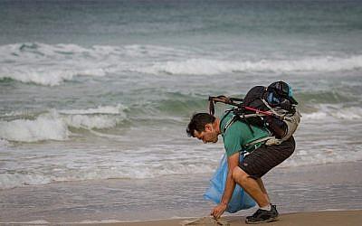 Le blogger israélien Gil Drori ramasse une sac plastique sur la plage de Beit Yanai le 23 novembre 2018, lors de son voyage de 9 jours pour sensibiliser sur le effets néfastes de la pollution d'objets plastiques jetables sur la mer Méditerranée. (Meir Vaknin/Flash90)