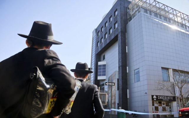 Des jeunes hommes s'arrêtent pour observer l'opération de police devant le Musée des Enfants juifs après une alerte à la bombe, jeudi 9 mars 2017 dans le quartier de Brooklyn de New York.(AP/Bebeto Matthews)