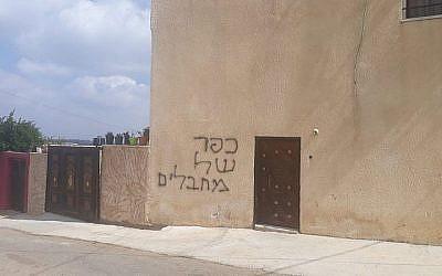 """Un mur peint au graffiti avec la phrase """"village de terroristes"""" dans un crime raciste au village cisjordanien de Deir Istiya, le 18 juin 2019 (Crédit : B'Tselem)"""