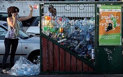 Une femme jette une bouteille dans un bac de recyclage du centre de Jérusalem. (Crédit photo : Nati Shohat/Flash90)