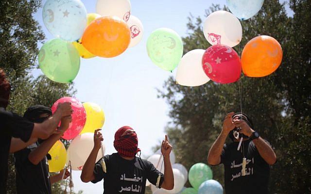 Des jeunes Palestiniens préparent des ballons incendiaires à envoyer en Israël à l'est du camp de réfugiés de Bureij, dans la bande de Gaza, le 31 mai 2019 (Crédit : Hassan Jedi/ Flash90)