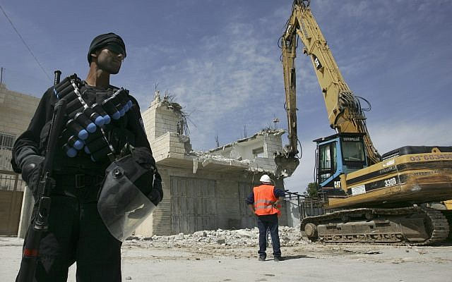 Photo d'illustration : Un agent de police israélien se tient près d'une pelleteuse lors de la démolition d'une maison palestinienne dans la banlieue de Sur Baher, à Jérusalem-Est, le 7 avril 2009 (Crédit : Kobi Gideon / FLASH90)