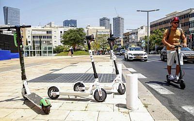 Des utilisateurs de trottinettes électriques dans les rues de Tel Aviv, le 30 mai 2019. (Crédit : JACK GUEZ / AFP)