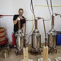 Le distillateur américano-palestinien Nader Muaddi attend que l'alcool soit distillé dans le village de Beit Jala, en Cisjordanie, près de Bethléem, le 16 juin 2019. (Crédit : HAZEM BADER / AFP)