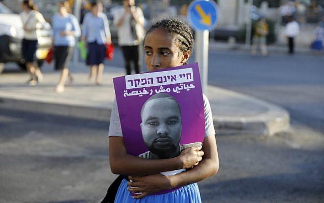 Une Israélienne tient une affiche à l'effigie de Solomon Tekah, un Israélien d'origine éthiopienne tué par un policier, pendant des manifestations dénonçant le racisme dont cette minorité fait l'objet, le 2 juillet 2019. (Crédit : MENAHEM KAHANA / AFP)