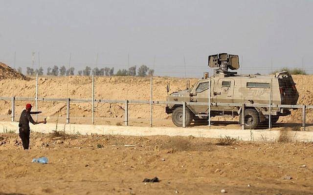 Un manifestant palestinien jette un cocktail molotov vers un véhicule militaire israélien durant des manifestations le long de la frontière avec Israël, à l'est de Khan Yunis, dans le sud de la bande de Gaza, le 5 juillet 2019 (Crédit :  SAID KHATIB / AFP)