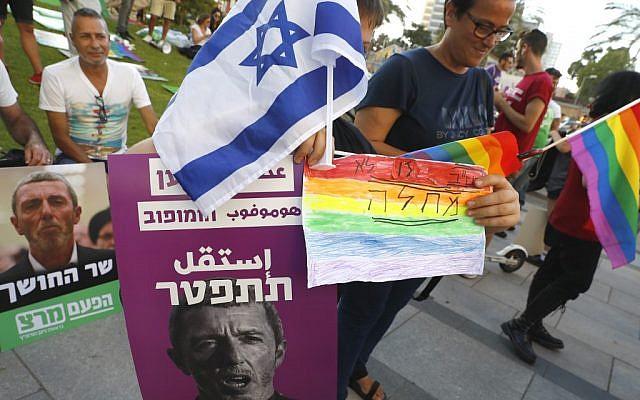 """Des membres de la communauté LGBT tiennent une banderole en hébreu """"Un raciste homophobe doit démissionner"""" lors d'une manifestation contre le ministre de l'Éducation Rafi Peretz à Tel Aviv le 14 juillet 2019. (Photo par JACK GUEZ / AFP)"""