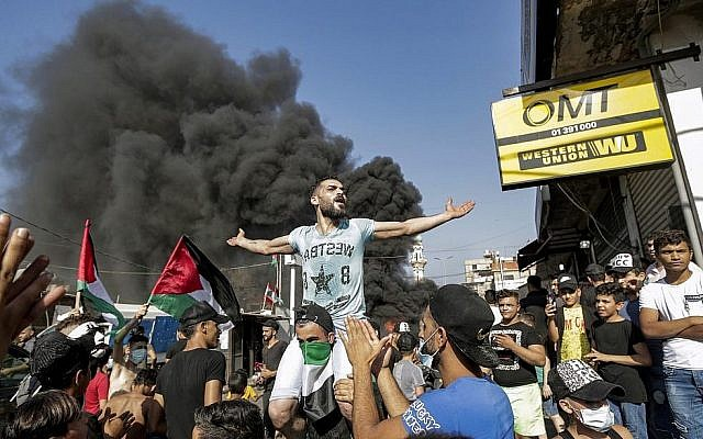 Un homme scande des slogans assis sur les épaules d'un autre homme portant un drapeau palestinien en bandana, alors que des manifestants bloquent la route principale devant le camp de réfugiés palestiniens de Burj al-Barajneh, au sud de Beyrouth, la capitale du Liban, le 16 juillet 2019. (ANWAR AMRO / AFP)