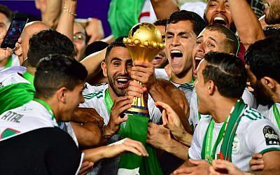 L'attaquant algérien Riyad Mahrez et ses coéquipiers célèbrent leur victoire en finale de la Coupe d'Afrique des nations 2019 contre le Sénégal au Stade international du Caire, le 19 juillet 2019. (Giuseppe CACACE / AFP)