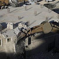 Les forces israéliennes de sécurité se préparent à démolir des immeubles en construction palestiniens promis à la destruction dans le quartier Wadi al-Hummus, adjacent au village palestinien de Sur Baher, à Jérusalem-Est, le 22 juillet 2019 (Crédit : Ahmad GHARABLI / AFP)